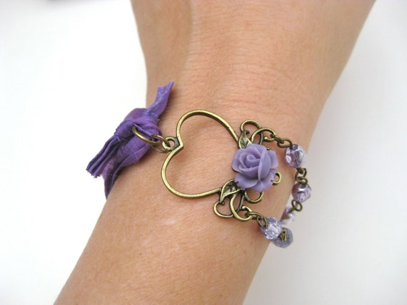 She Wore Purple Then - Vintage purple bracelet featuring an antique brass heart charm with flower, purple glass beads, and silk sari ribbon