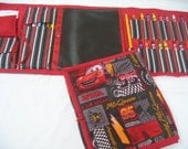 Black McQueen Art Travel Tote in a colorful print complete  with chalkboard, chalk, eraser, paper, crayons pencil, and colored pencils