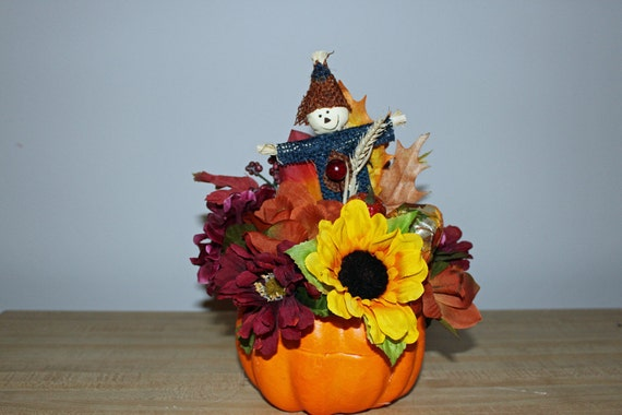 Pumpkin centerpiece , scarecrow, sunflowers, mums, leaves, berries  and ribbon