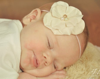 Small Vintage Soft Pink Flower Headband with ivory white and gold pearl center on a skinny light pink elastic headband