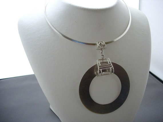 Torque necklace with cage and circle pendant