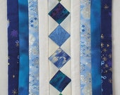 Fiber Wall Art, a tiny Zen quilt with stars and sparkling snowflakes in shades of blue, white and silver.