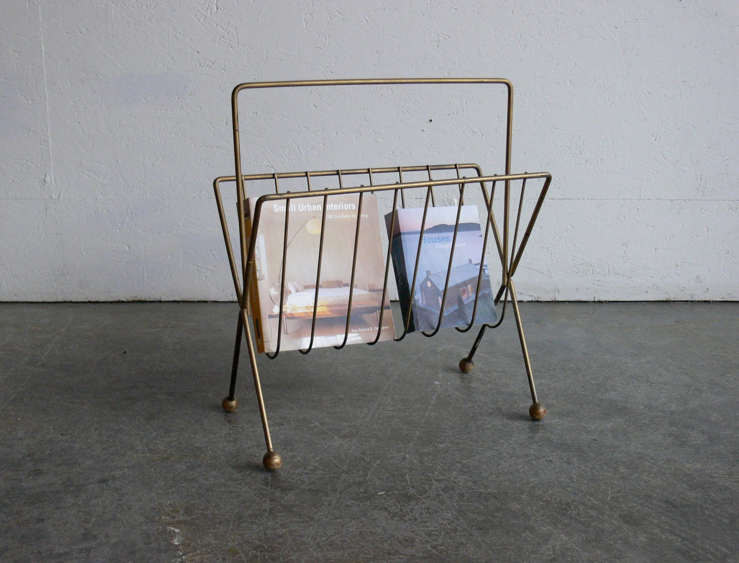 This magazine rack is designed with a rectangular This magazine rack is designed with a rectangular wood body with open sides front and back metal grill trellis design curved tops and dividers that form 3 compartments offering convenient storage and display options for homes and offices. This magazine rack's 4 tapered block feet provide sturdy support and stability.