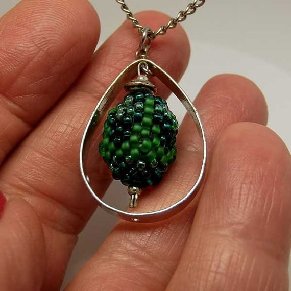 Beadwork necklace with a spinning  forest of seed beads suspended in a silver teardrop frame