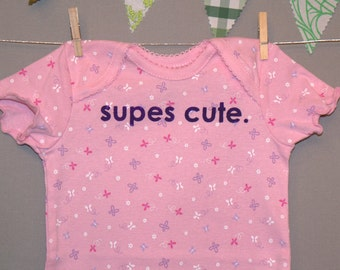 supes cute. --- pink patterned bodysuit, size 6 - 9 months.
