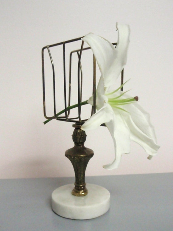 Hold on to this. A vintage brass napkin or letter holder with marble base.