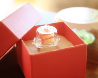 A slice of Birthday cake on a cake cover scallop dome  ring