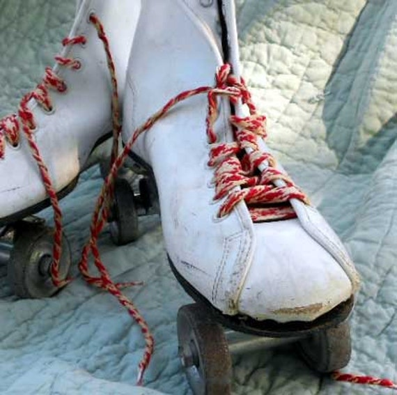 Vintage Roller Derby skates from the 1960s with metal wheels and red and white laces, size 7