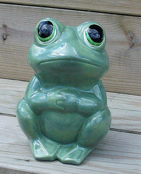 Ceramic bug-eyed frog hands crossed