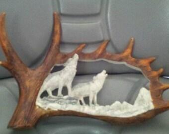 Carved Antler wolves on rocks mountain