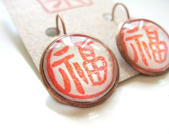 Good fortune. Copper earrings handprinted in red
