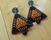 Handmade drop earrings made with woven patterned seed beads in a 3D triangular shape with black onyx dangle at the base by Dee Andersen