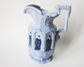 Unusual Embossed Blue Ceramic Pitcher with Bas Relief Figures