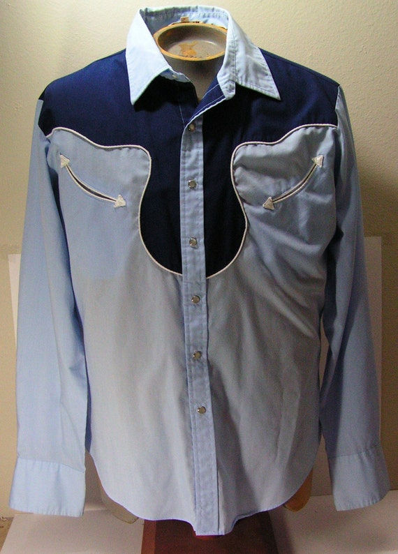 Ladies Long sleeve Western Shirt * 1 Point Curved Back Yoke * white Poplin Inside Trim * Cover Stitch Detail * Embroidered Logo On Front * white pearl snaps AND Blue pearl snaps Both Used * 3 snap Cuff * Waist Darts * Garment Washed *.