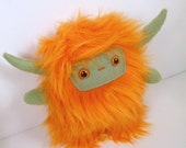 Nin the horned plush monster orange and olive green stuffed animal