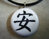 Japanese kanji symbol for PEACEFUL-SAFE hand carved on a Polymer clay white granite color background. Pendant comes with a FREE 3mm necklace