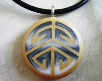 Shadow Puzzle circle hand carved on a polymer clay mustard color background. Pendant comes with a FREE Necklace