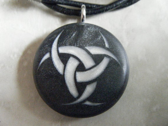 Triple Goddess hand carved on a black pearl background. Pendant comes with a 3mm leather necklace.
