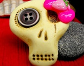 Mini sugar skull brooch with a pink bow and a brown button eye. Vanilla, strawberry and chocolate is a great combination for a mini monster