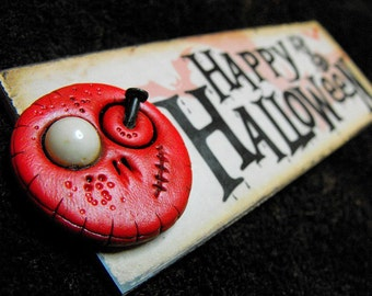 Happy Halloween plaque with a lovely red mini skull. A happy skull for a happy celebration. Also can be a magnet