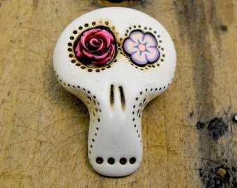White sugar skull with floral eyes: a pink rose and a lavender daisy. Brooch, keychain, pendant or magnet (you choose)