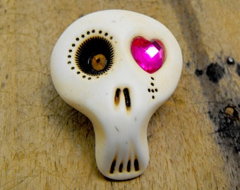 White sugar skull brooch with a shiny fuchsia heart in his eye. Surprised face. Brooch, keychain, pendant or magnet (you choose)
