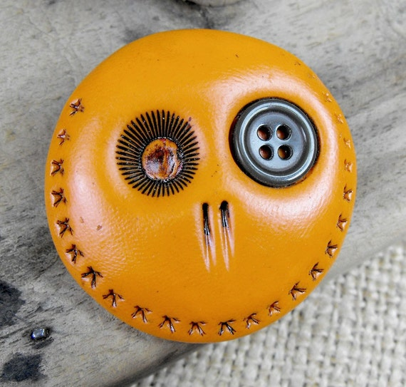 Happy orange mini skull brooch with a khaki green button in is eye