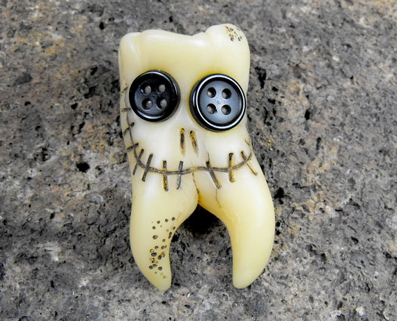 Smiling molar monster. Human teeth brooch with two roots and two buttons in his eyes