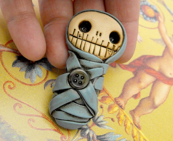 Adorable baby mummy brooch in blue. Creepy and cute. Lovely and primitive. Very young and very dead