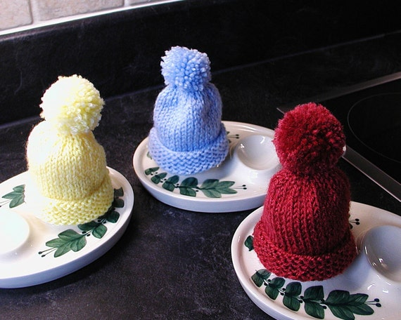 Set of four hand knitted egg cosies with pom poms in a variety of colours