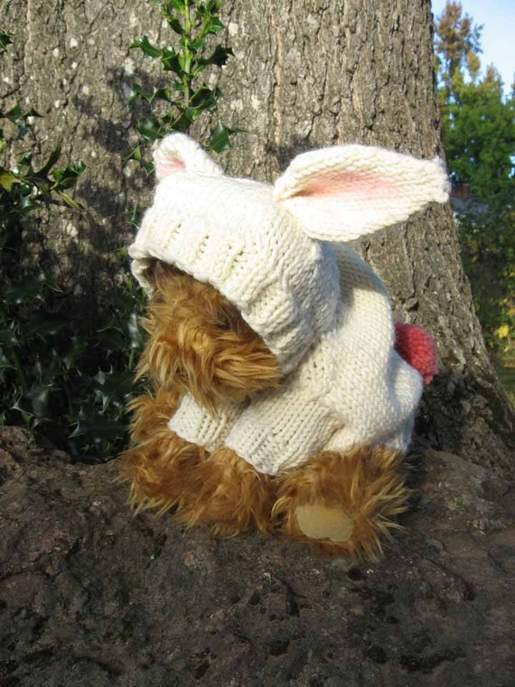 A hooded dog sweater with decorative bunny ears and pompon tail.