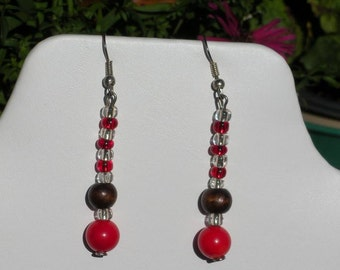 Red coral dangling earring with brown wooden beads and transparent seed beads.