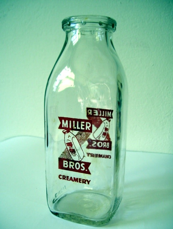 old glass pint milk bottle with red painted lettering and picture