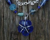 Blue glass bead necklace with wire wrapped flower pendant