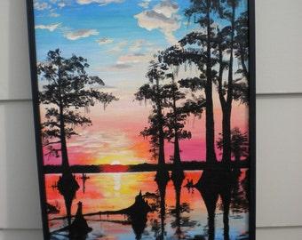 Original art acrylic painting titled Peaceful Energy, trees lake water, cloudy sky, sunrise sunset yellow orange red blue black silhouette