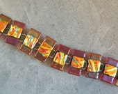 Translucent red iridized and orange dichroic bracelet.