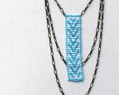 sky blue and white graphic necklace