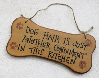 Funny Sign Dog Hair a Condiment  in This Kitchen on Bone Shaped Sign