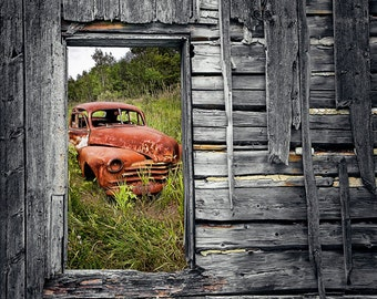 Rusted Vintage Car seen through the Window of a Weather Beaten Wall shows the Ravages of Time Landscape Photograph