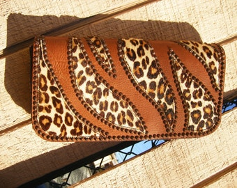 Your spots are showing...Leopard print fur and brown leather clutch