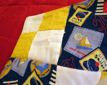 Dolphin Cove Little Sailor baby quilt in nautical navy, yellow, white and red