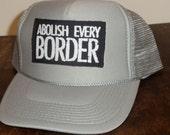 abolish every border trucker hat