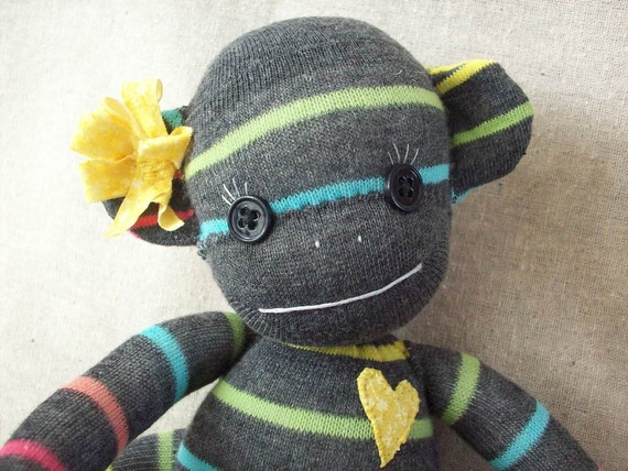 A sock monkey doll in grey with rainbow stripes, Peta