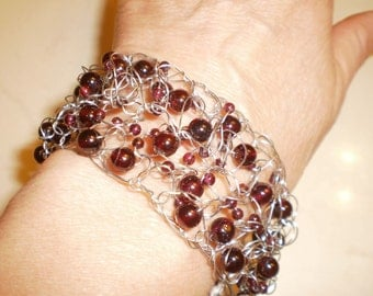 January is for garnets. Crocheted wire bracelet with deep red garnet beads.