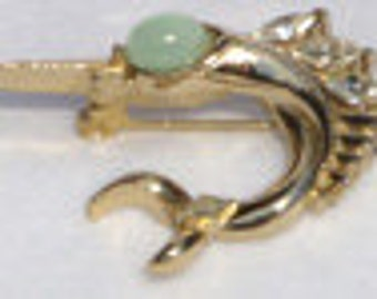 Vintage jewelry brooch in  gold tone flying fish with sea foam green eye and clear rhinestone fin brooch