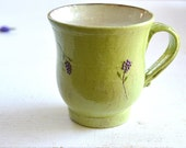 An olive-green mug with purple flowers