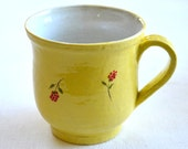 A  sun-yellow mug with red flowers