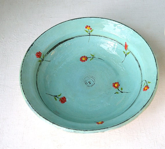 A turquoise- blue bowl with flowers