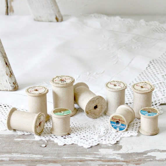 9 white wooden spools
