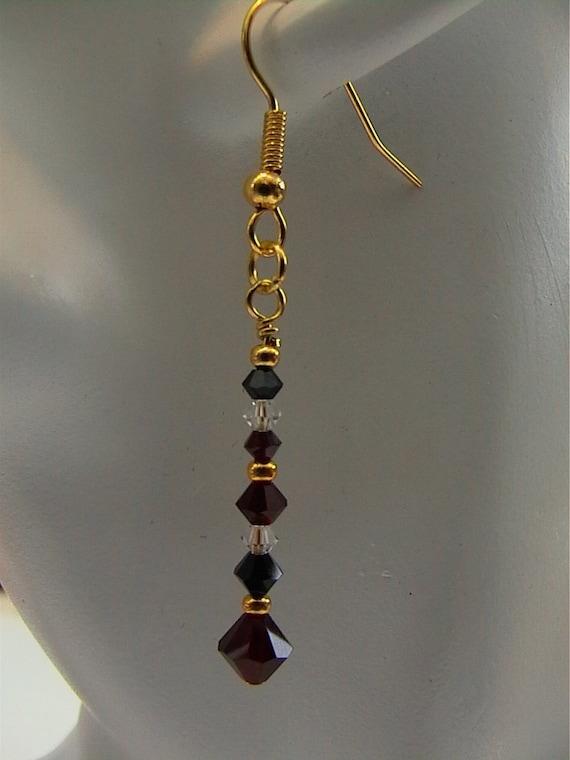 Harlequin -  Swarovski crystals in Jet Black, deep red Garnet and Clear. Gold-plated